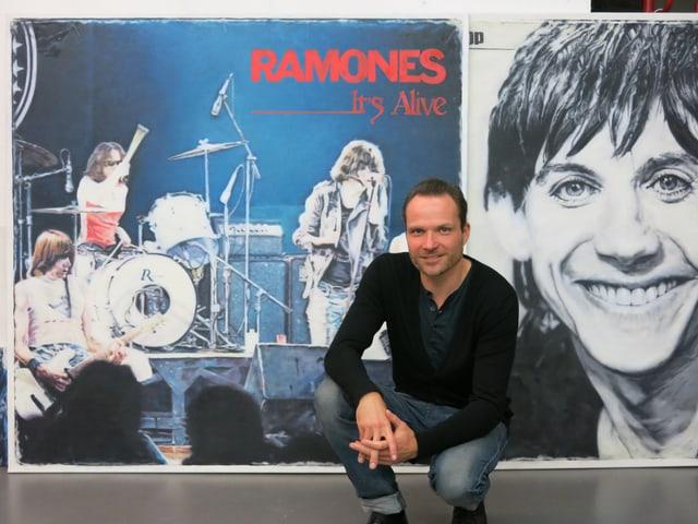 Künstler Mart Meyer vor übergrossen Bildern von Iggy Pop und den Ramones