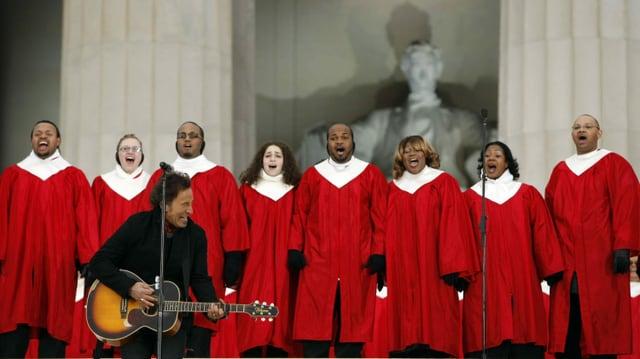 ein Mann mit Gitarre vor einem Chor in roten Gewändern