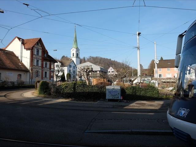 Im Vordergrund rechts ist ein Tram, im Hintergrund sind Kirche und alte Häuser zu sehen.