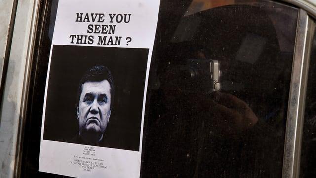 Ein Fahnundsfoto von Janukowitsch auf einem Auto.
