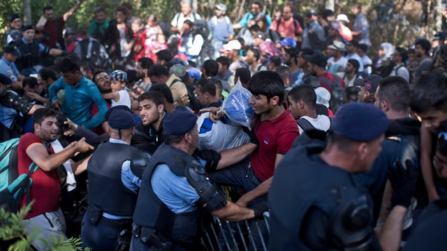 Persunas che sa fultschan cun tutta forza sur las barricadas da la polizia.
