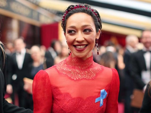 Schauspielerin Ruth Negga im roten Kleid und mit blauer Schleife.
