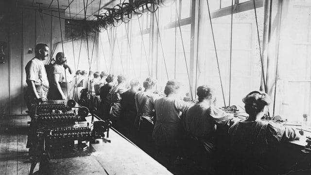 Einblick in eine Uhrenfabrik. Arbeiter sitzen an einer langen Werkbank.