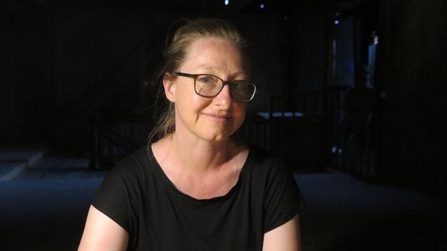 Eine schwarz gekleidete Frau mit dunkler Brille.