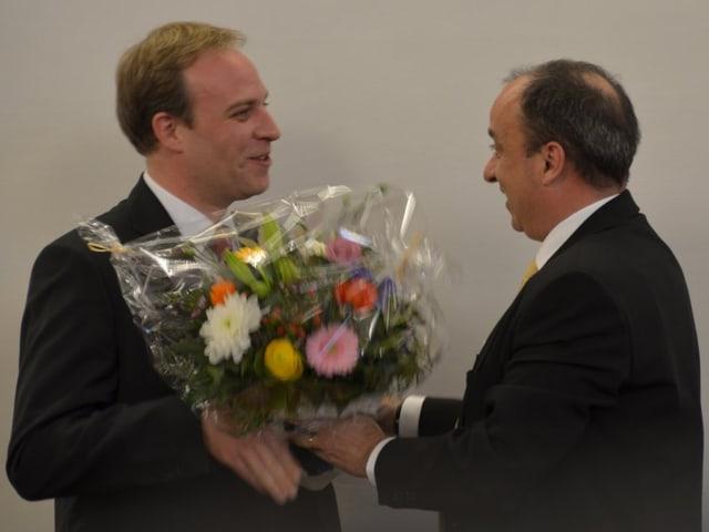 Mann überreicht anderem Mann einen Blumentstrauss und schüttelt die Hand