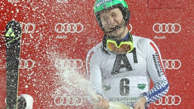 Skifahrer auf Podest feiert mit Champagner