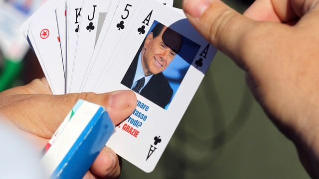 Eine Hand hält Spielkarten in der Hand. Eine davon trägt das Konterfei Silvio Belrusconis.