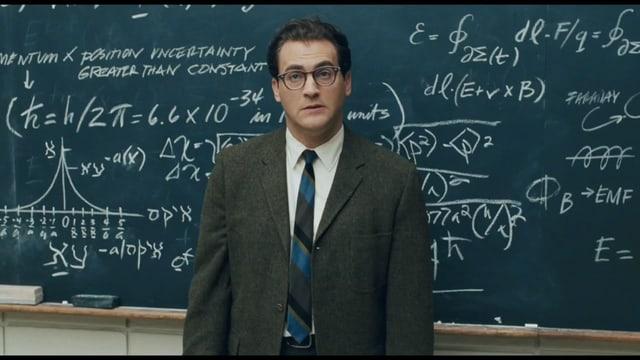 Das Bild zeigt einen Mann in Schlips vor einer Wandtafel, die mit physikalischen Formeln vollgeschrieben ist.