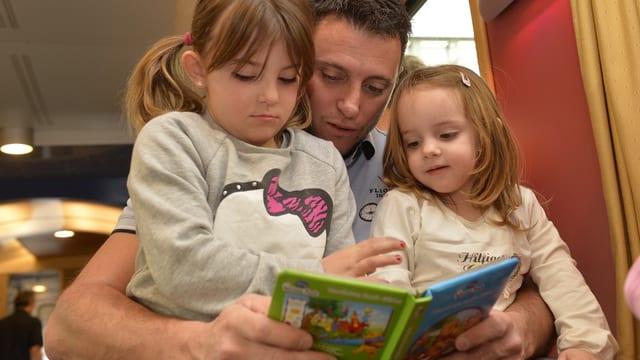 Ein Vater mit seinen beiden Töchtern, der Vater hat ein Kinderbuch aufgeschlagen.
