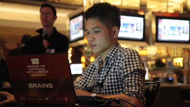 Ein junger Mann sitzt am Laptop in einem Kasino.