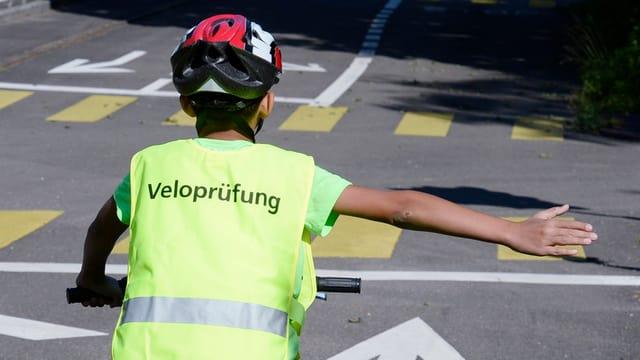 Kind mit einer West mit der Aufschrift Veloprüfung streckt den rechten Arm hinaus zum Abbiegen
