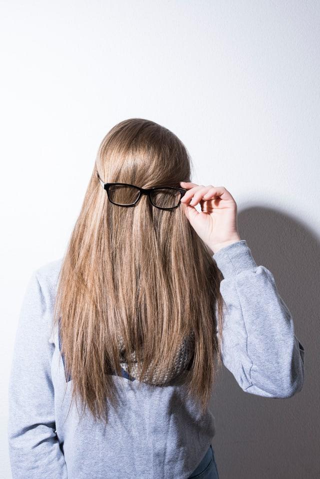Eine Frau hat die Haare nach vorne gekämmt, so dass man sie nicht kennt. Und eine Brille aufgesetzt.