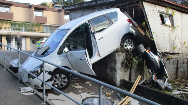 Auto hängt über einer Mauer, dahinter eine zerstörte Garage