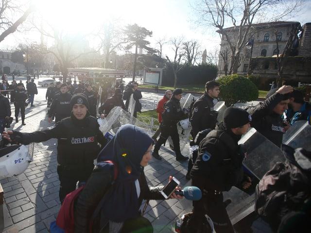Polizisten eskortieren Passanten