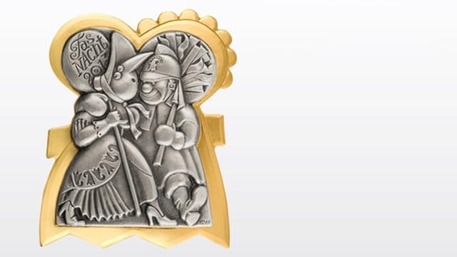 Die Plakette zeigt eine Alte Tante und einen Baselbieter Chienbesenträger
