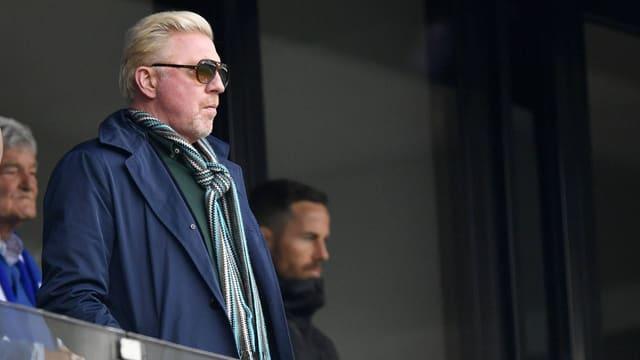 Becker steht mit Sonnernbrille.