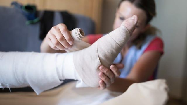 Eine Spitex-Pflegerin legt einen Verband an