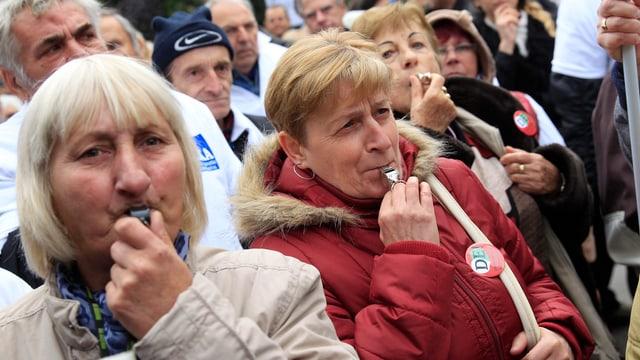 Mehrere ältere Frauen mit Trillerpfeifen.