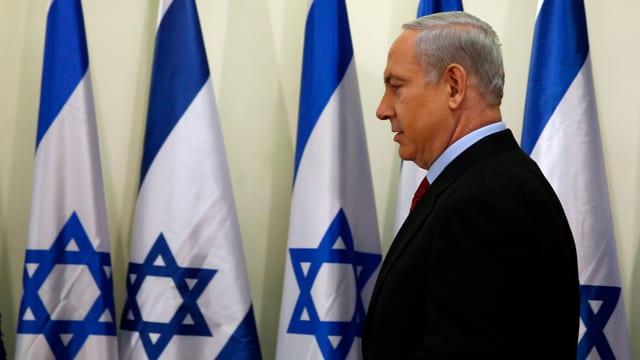 Benjamin Netanjahu geht mehreren Israel-Flaggen entlang.