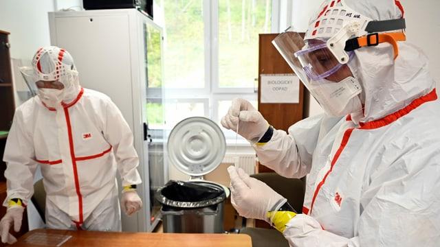 Mitarbeiter in Schutzmontur verabeiten Corona-Tests.