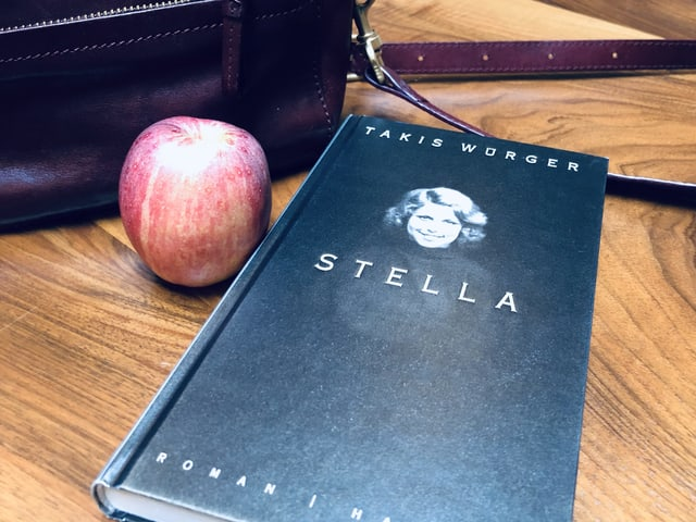 Der Roman «Stella» von Takis Würger liegt auf einem Tisch. Daneben Handtasche und Apfel