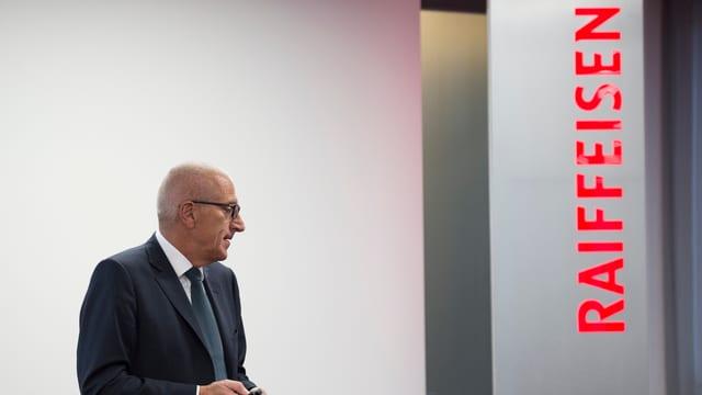 Pierin Vincenz neben einem Raiffeisen-Logo, zur Seite schauend.