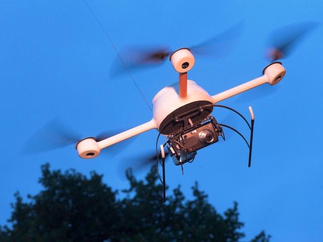 Ein unbemannter Kleinhelikopter mit Kamera im Flug.