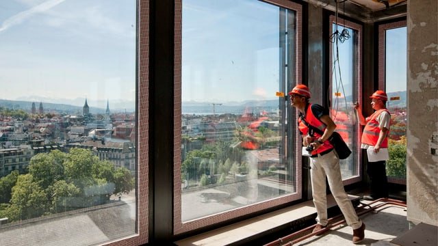 Zwei Menschen mit roten Warnwesten blicken aus einem Rohbau an der Europaallee auf die Stadt Zürich hinab.