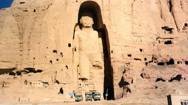 Buddhastatue in einer Felsnische. Davor stehen Autos. Sie sehen munzig aus.