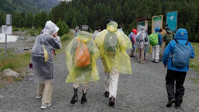 Asiatische Touristen tragen dicke Jacken und Regenschütze bei ihrem Besuch in der Nähe von Pontresina.