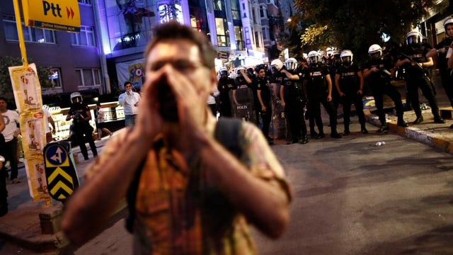 Ein Mann vor einer Wand aus Polizisten