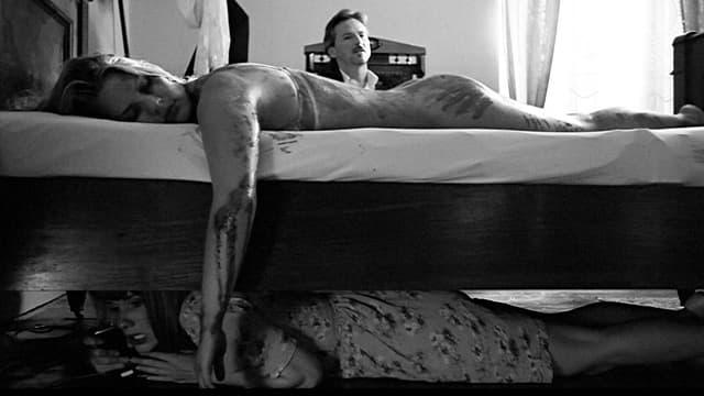 Eine blutige Frau liegt auf dem Bett. Unter dem Bett versteckt sich eine andere Frau. Und im Hintergrund sitzt ein Mann im Anzug.