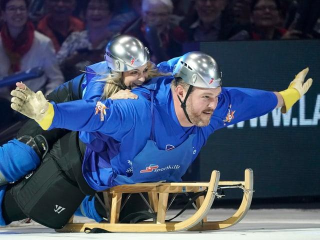 Silvana Tirinzoni und Christian Stucki liegen zu zweit auf einem Schlitten.