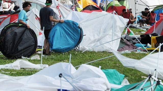 Zerstörte Zelte. Openair-Besucher suchen ihre Sachen zusammen.
