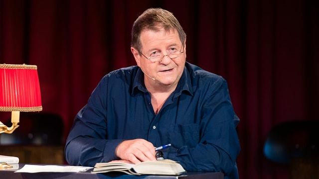 Hanspeter Müller-Drossaart sitzt an einem Tisch und liest aus einem Buch vor.