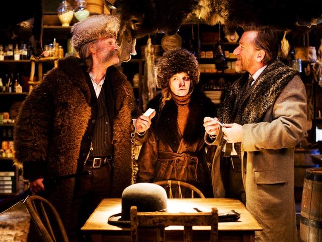 Zwei Männer und eine Frau diskutieren in einer Hütte während eines Schneesturms.
