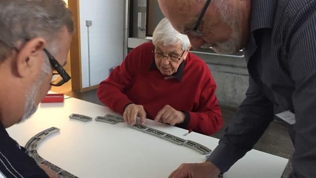 Ältere Menschen stehen um einen Tisch