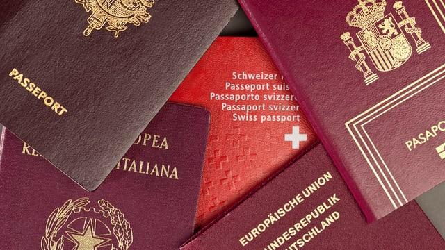 Mehrere Pässe mehrerer Länder leigen auf einem Haufen, Dazwischen liegt ein Schweizer Pass.
