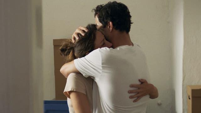 Eine Frau und ein Mann umarmen sich in einer leeren Wohnung.