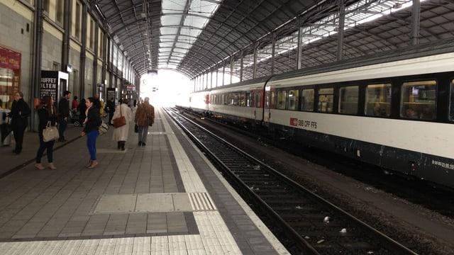 Bahnhof Olten, Blick aufs Perron, daneben steht ein Zug still. In der Ferne sieht man das Licht durch das Ende des Pavillons scheinen.