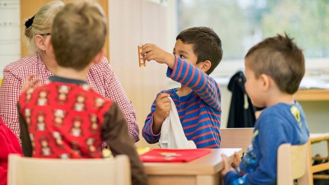 Kindergartenkinder sitzen um einen Tisch und spielen.