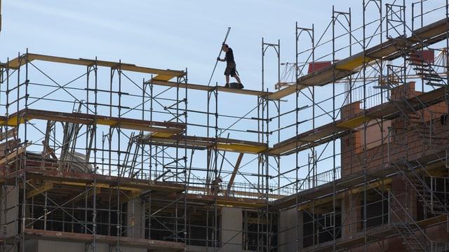 Arbeiter von Ferne zuoberst auf einen Baugerüst auf einer Baustelle im Gegenlicht