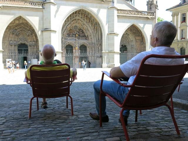 Zwei Herren sitzen auf Stühlen im Schatten und schauen das Münster an.