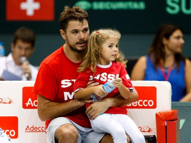 Alexia sitzt auf dem linken Bein von Wawrinka, der auf der Bank am Court sitzt.