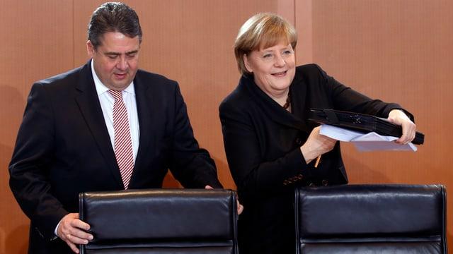 Vizekanzler Sigmar Gabriel und Kanzlerin Angela Merkel setzen sich an einen Verhandlungstisch.