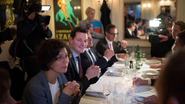 Maudet und seine Frau sitzen in einem Restaurant an einer gedeckten Tafel - im Hintergrund ein Kamermann und eine Frau mit Mikrofon.