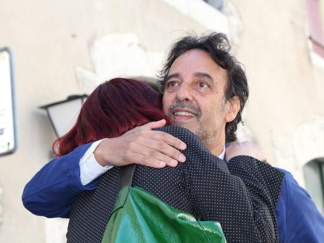 Ein Mann mit blauem Jackett umarmt eine Frau mit roten Haaren und grüner Tasche