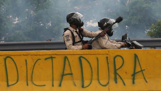 Polizisten auf einer Motorrad mit Tränengas-Gewehr.