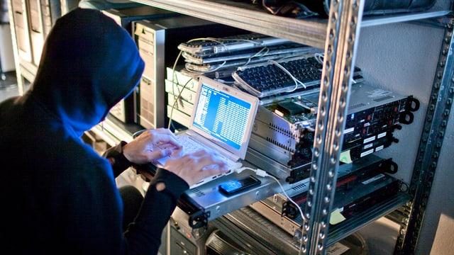 Ein Mann sitzt in einem dunklen Raum an einem PC.