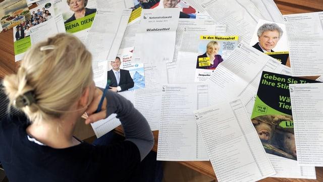 Eine Frau sitzt vor einem Haufen Wahlunterlagen.